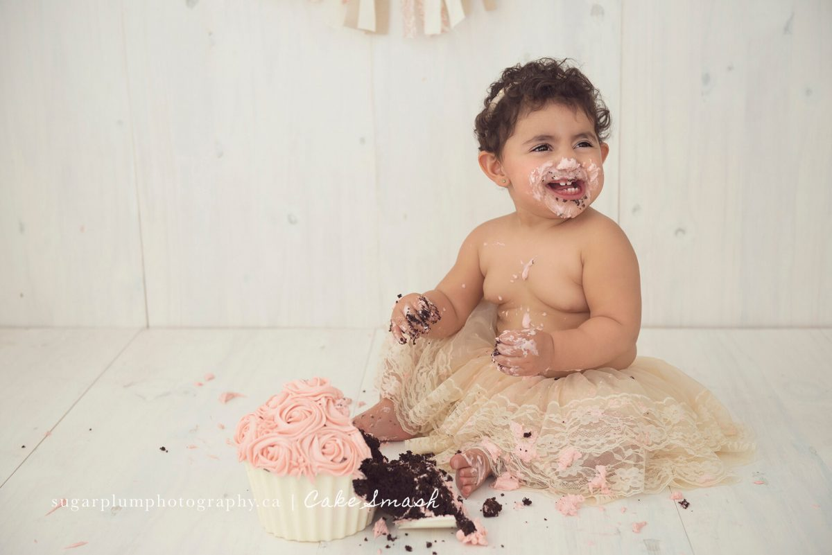 Baby girl with cake on face in tutu laughing