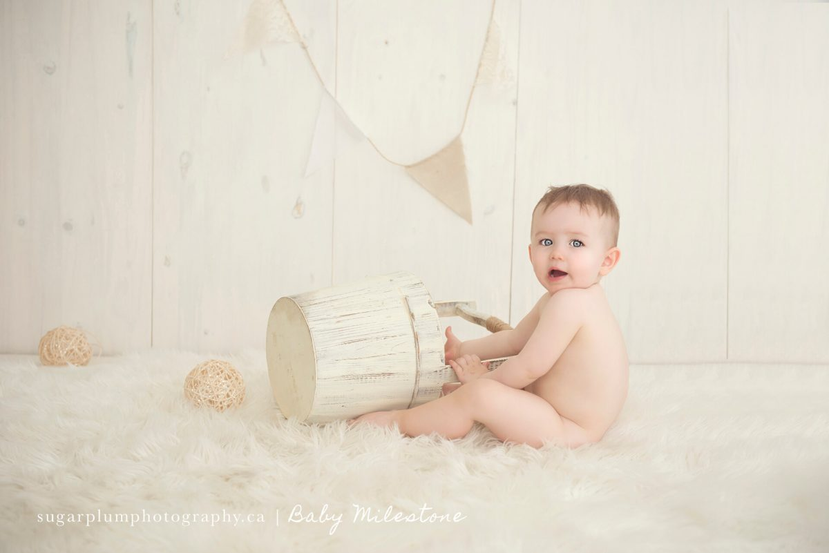 Baby playing with bucket and balls on wooden set