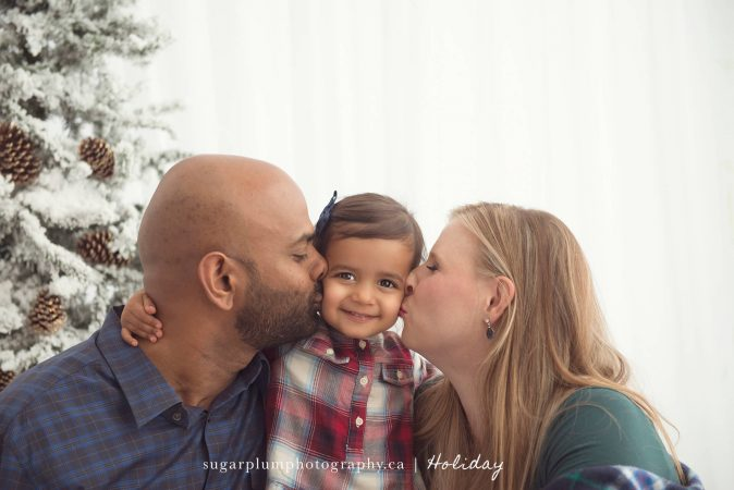 Mother and father kissing daughter for Christmas card