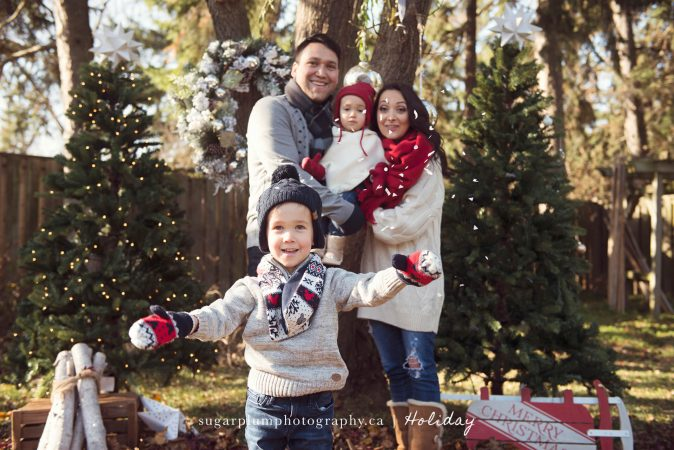 Toddler boy tossing snow with family
