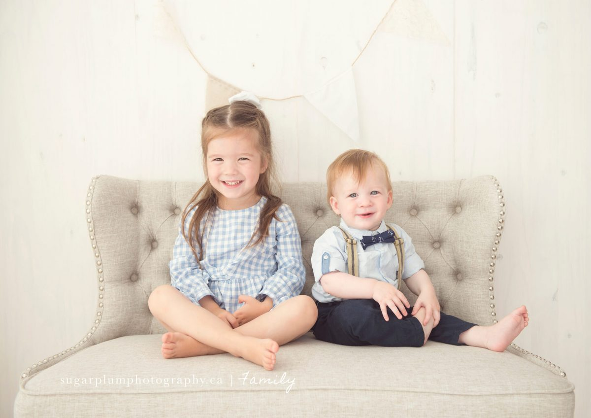 Siblings sitting on couch smiling