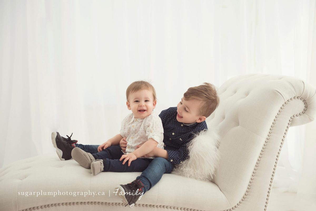 Brothers sitting on chaise in studio