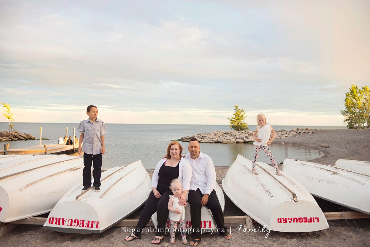 Family posing on beach sitting on boats
