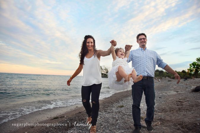 Family on beach with toddler daughter swinging