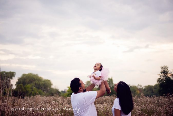 Father holding up daughter in flower field with mom