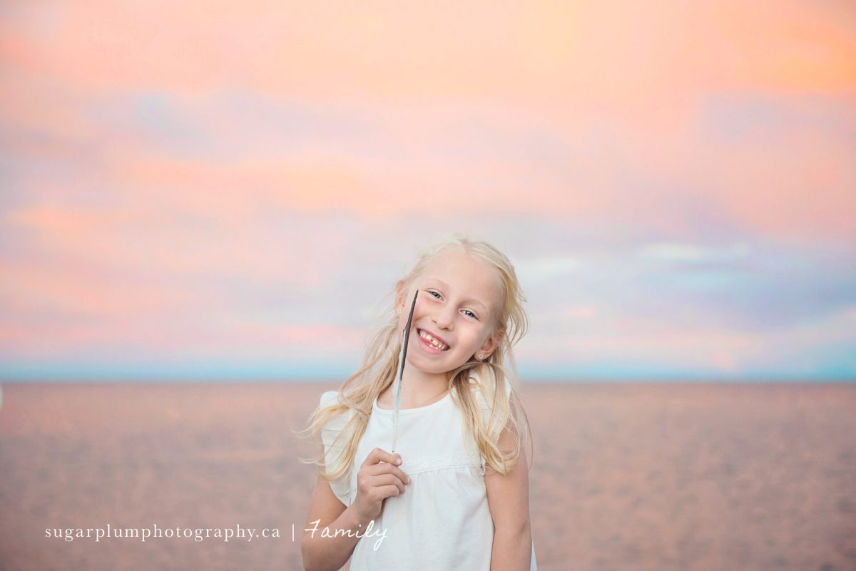 Smiling girl with feather on beach