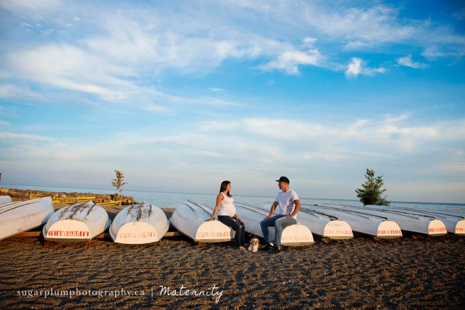 Pregnant couple sitting on boats on beach