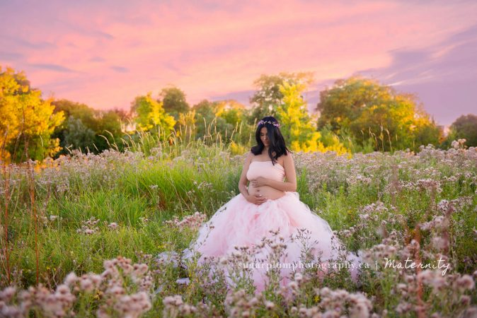 Pregnant woman in maternity gown in flower field