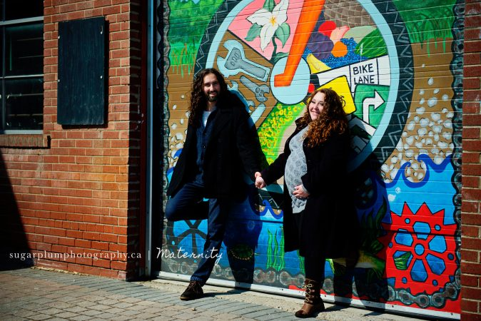 Pregnant couple standing against graffiti wall laughing