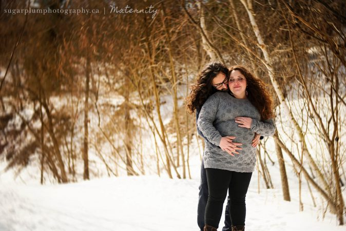 Pregnant couple embracing on wooded winter trail