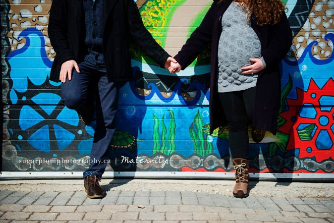 Pregnant couple against graffiti wall holding hands