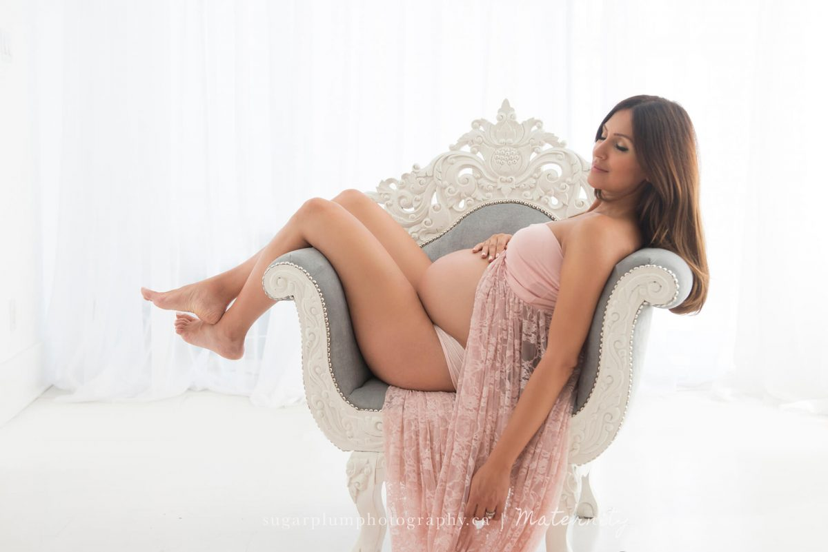 Pregnant woman with legs over armchair holding belly