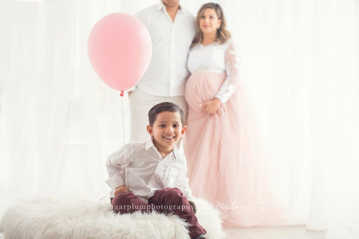 Toddler son holding ballon with parents in background