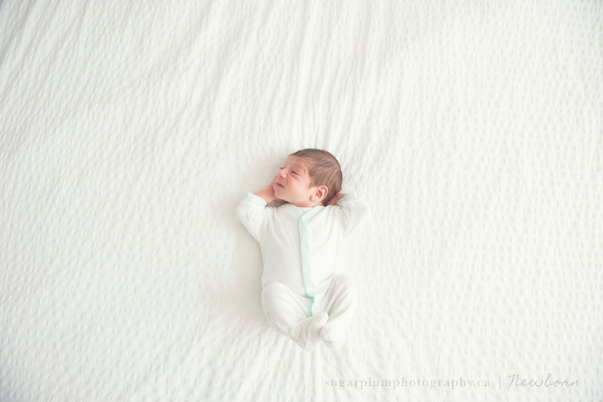 Newborn stretching on master bed in home