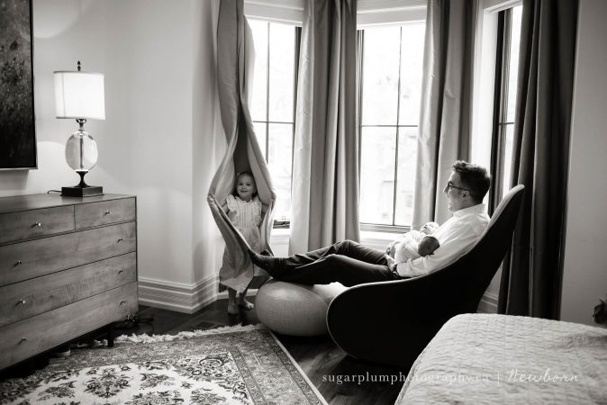 Toddler playing peekaboo with father and twin newborn siblings