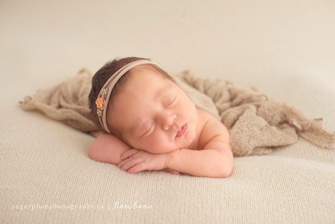 Face feature of baby girl on blanket, sleeping on arms
