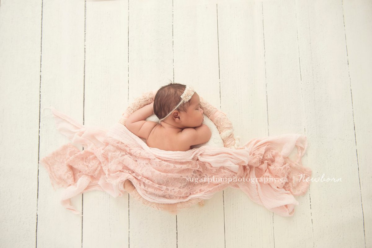 Aerial of newborn in lace basket on wooden set