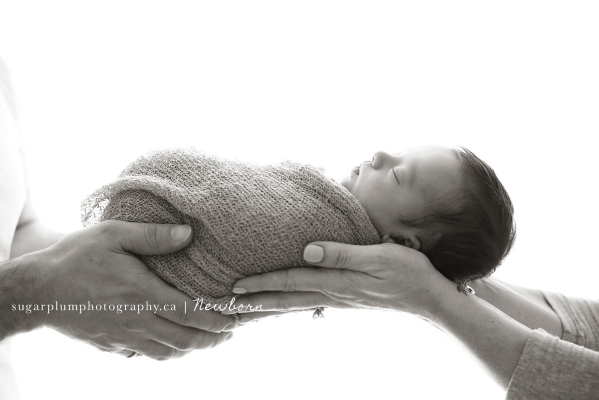 parent hands holding sleeping newborn