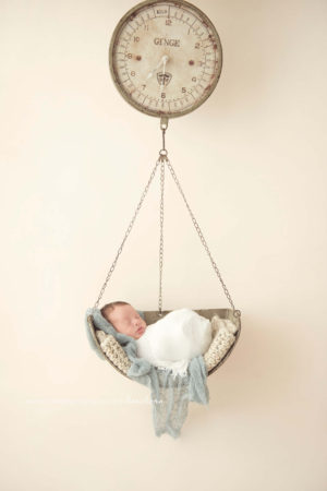 newborn hanging in scale