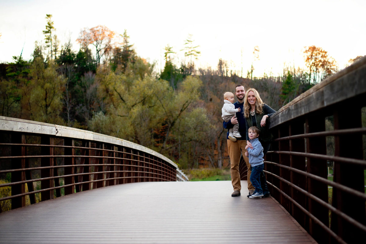 Family standing on side of bridge