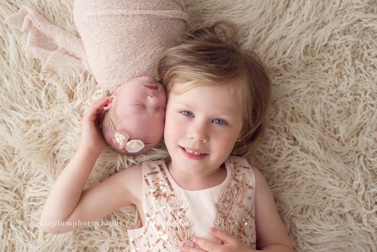 Sibling photography sister side by side with newborn baby