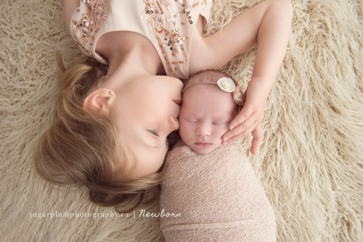 Sibling photography sister kissing baby