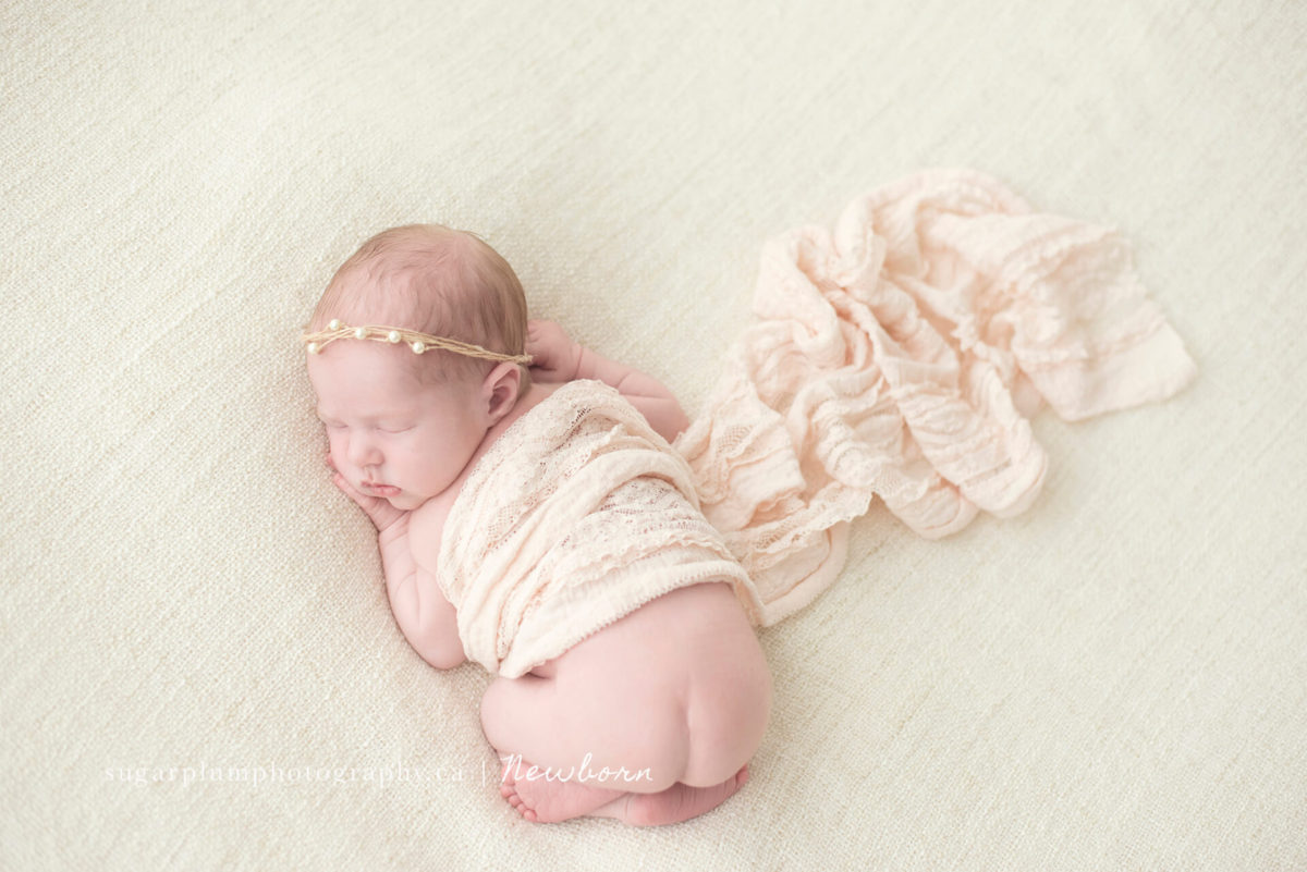 Aerial view of newborn baby in bum-up position on blanket
