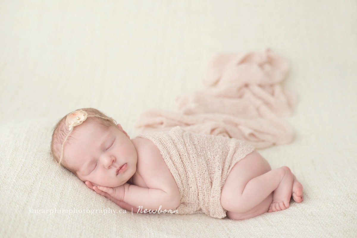 Newborn baby in side pose on blanket