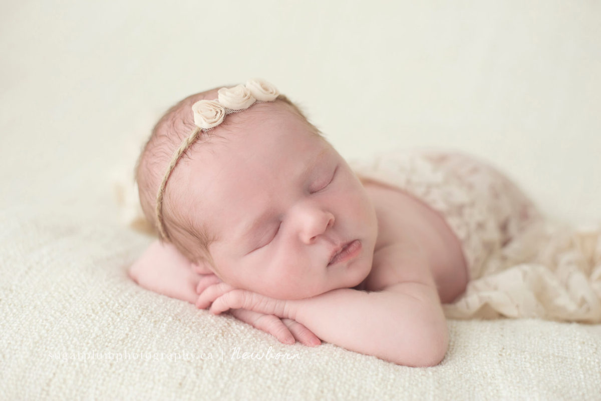 Newborn resting on folded arms