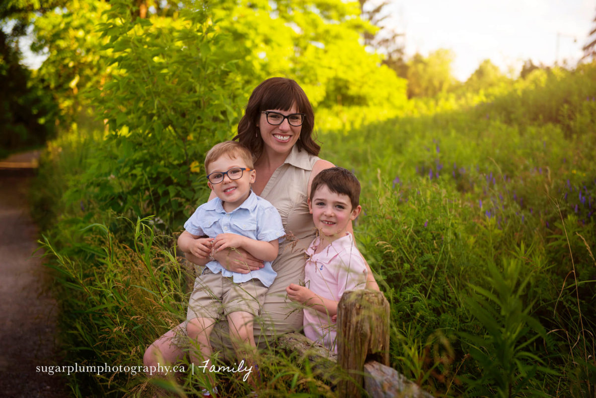 Mother with kids sitting on rustic wooden fence
