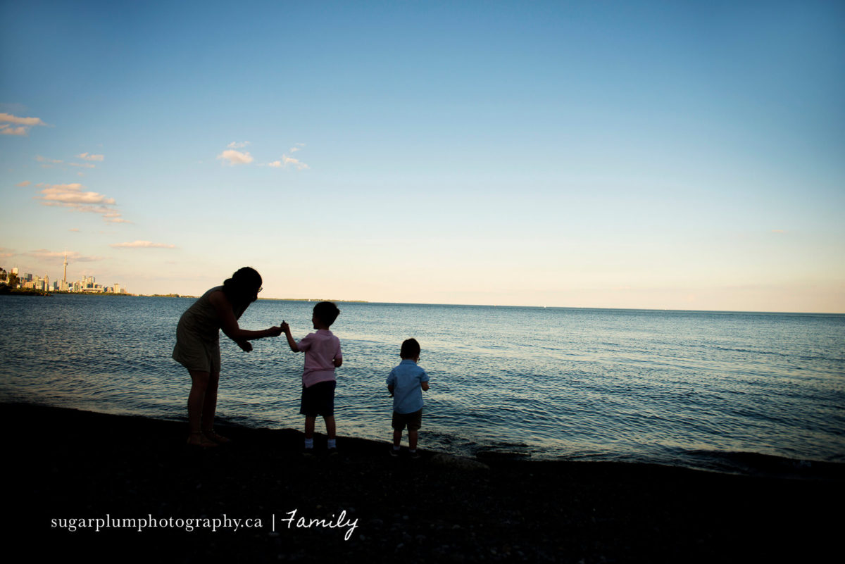 Silhouette of mother and children on beach in Toronto