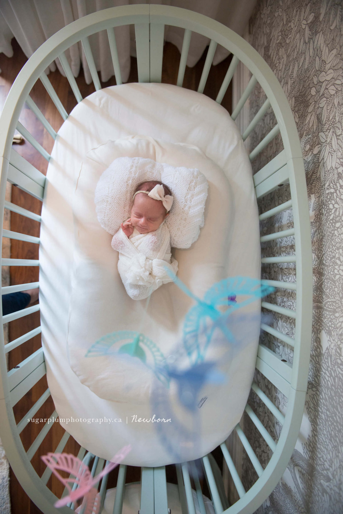 swaddled newborn in her crib