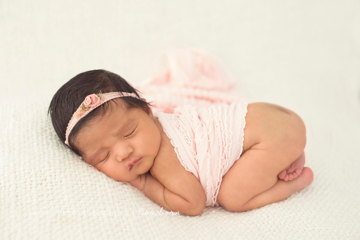 Bum up pose with pink headband on blanket