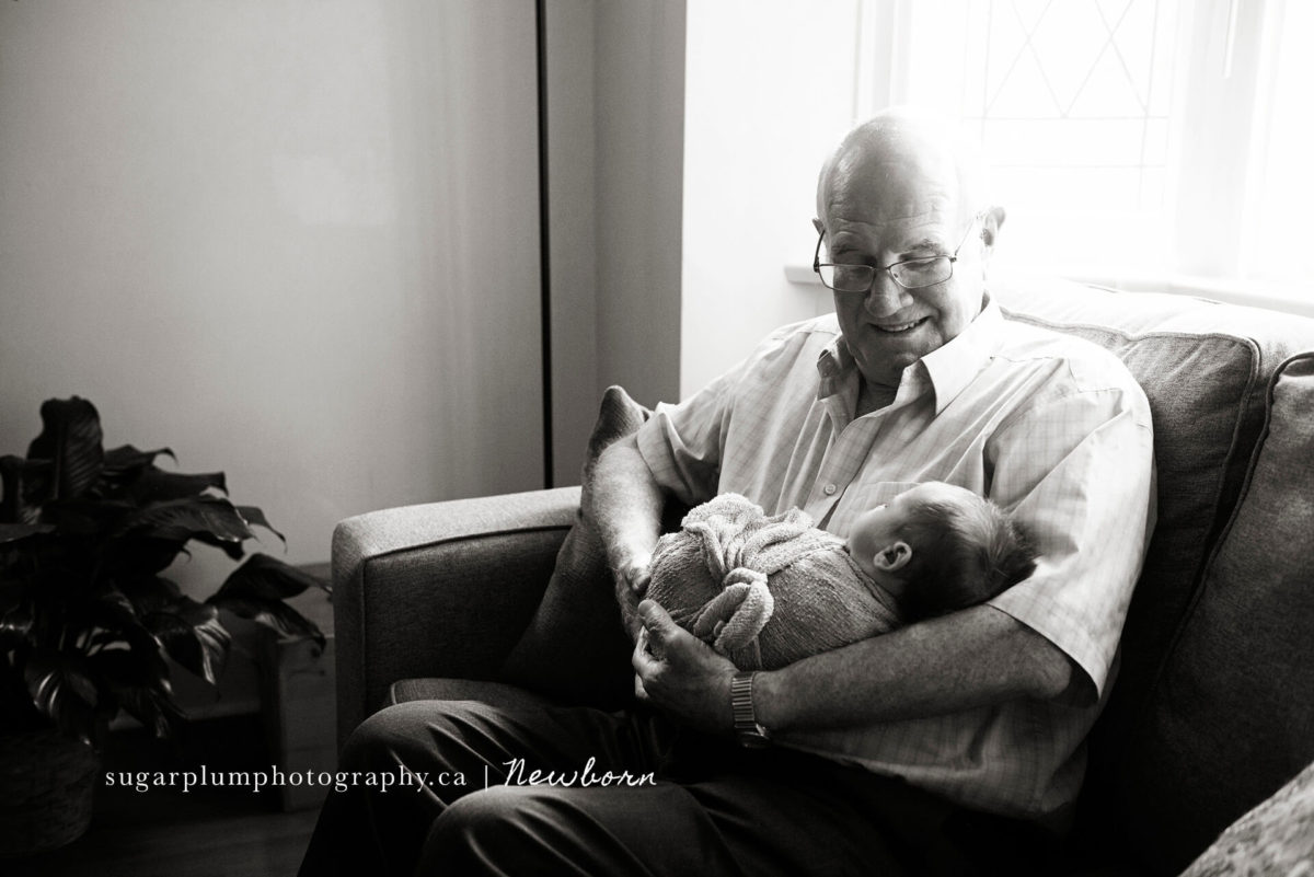 grandfather smiling at grandson on a couch, cradle pose