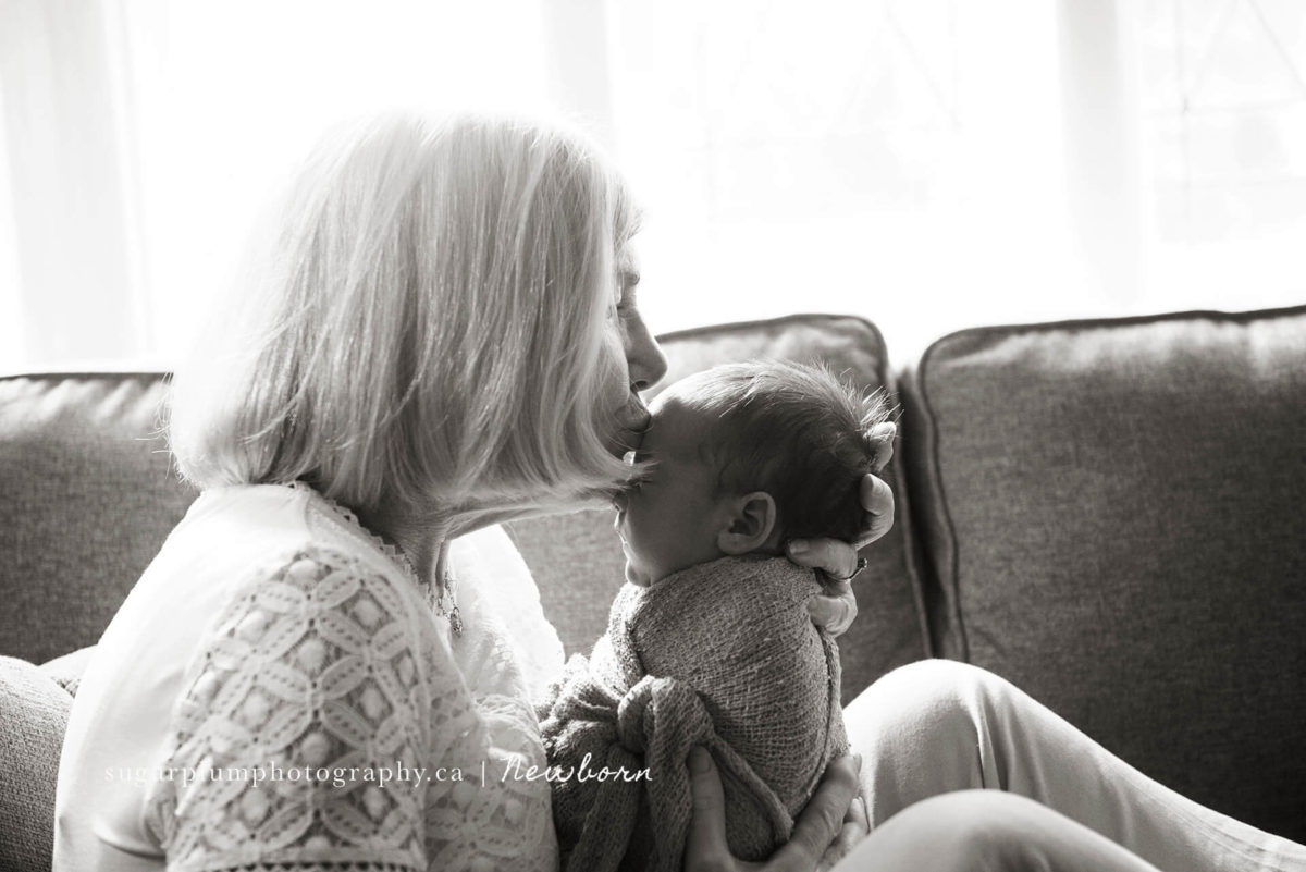 grandmother softly kissing grandson on forehead