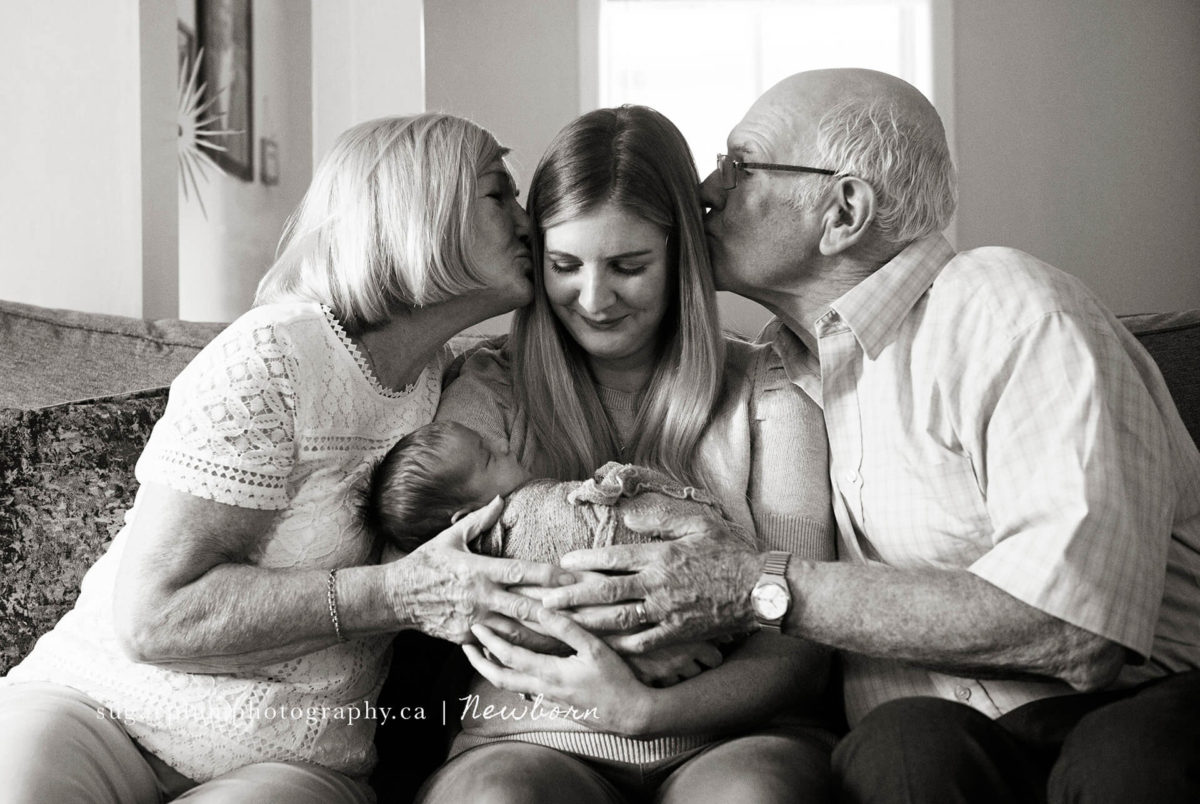 grandparents kissing daughter holding her son