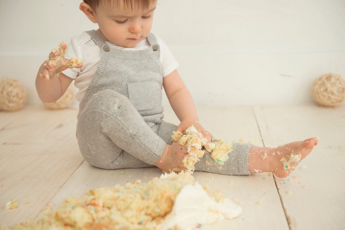 messy baby with cake on hands and feet