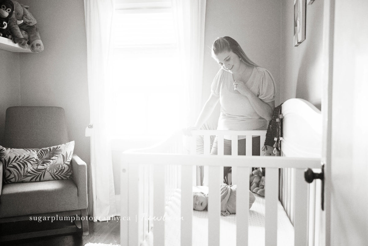 mom standing over baby in nursery