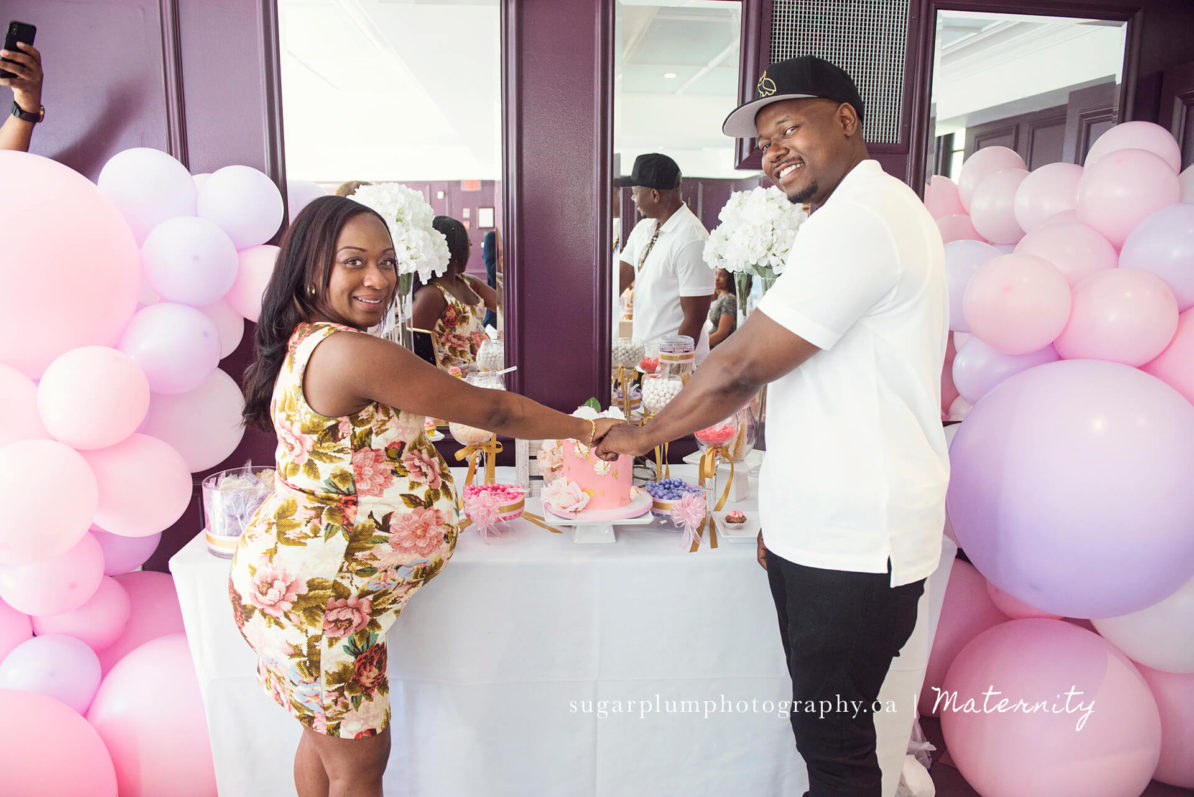 pregnant couple posing for cake ceremony