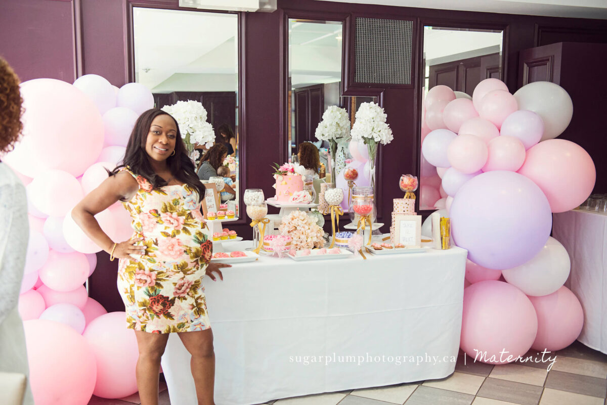 Pregnant mom posing next to candy station