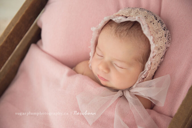 sleeping newborn girl wearing bonnet